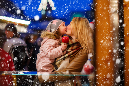 weihnachtsmarkt: Beatiful mother and little daughter eating crystalized sugared apple on German Christmas market. Happy family in winter clothes with lights on background. Family, tradition, holiday concept Stock Photo
