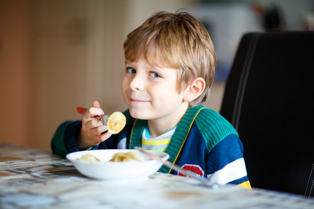 school canteen: Adorable niño de la escuela de comer pasta cubierta. Niño rubio en la cocina doméstica o en el comedor de la escuela del niño lindo y comida sana, ravioles o pelmeni ruso.