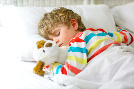 nightwear: Adorable little blond kid boy in colorful nightwear clothes sleeping and dreaming in his white bed with toy. healthy child with soft toy, peaceful sleep at home.