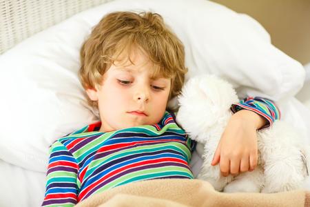Der entzückende kleine blonde Junge Junge in bunten Nachtzeug Kleidung schlafen und in seinem weißen Bett mit Spielzeug zu träumen. gesundes Kind mit weichem Spielzeug, ruhigen Schlaf zu Hause.