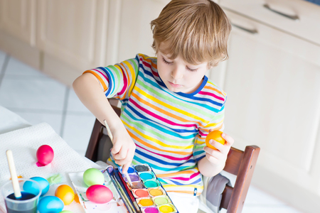 Little blond kid boy coloring eggs for Easter holiday in domestic kitchen, indoors. Child having fun and celebrating feast. Stock Photo