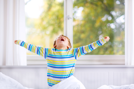 nightwear: Adorable happy little kid boy after sleeping in his white bed in colorful nightwear near big window with green and yellow autumn foliage. Funny happy child playing and smiling. Family, vacation, childhood concept Stock Photo