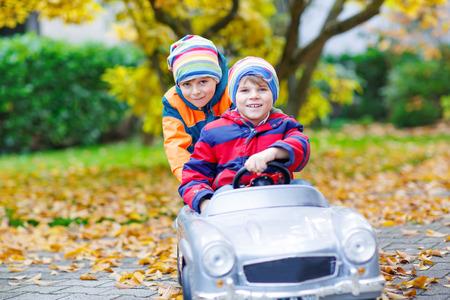 niño empujando: Dos gemelos felices los niños chicos divirtiéndose y jugando con gran viejo coche de juguete en el jardín de otoño, al aire libre. Hermano que empuja el coche de niño. La felicidad, diversión, tiempo libre en el parque de otoño. Foto de archivo
