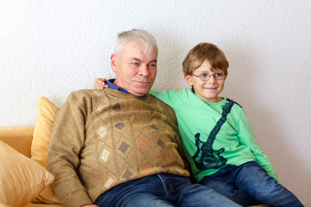 remote view: Little kid boy and grandfather watching tv at home. Preschool child and senior man enjoying cartoons on television. Sitting together on couch. people, children, television, friends and friendship concept