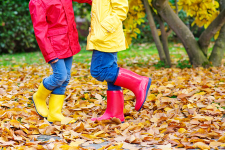 Two little children playing in red and yellow rubber boots in autumn park in colorful rain coats and clothes. Closeup of happy kids dancing and walking through fall autumnal goden leaves and foliage.