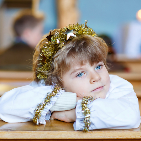quite: Beautiful little kid boy playing an angel in Christmas story in a church. Happy adorable blond child with lights and xmas tree on background. Stock Photo