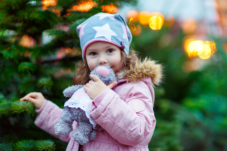 chirstmas: Cute little smiling kid girl with christmas tree. Happy child in winter clothes and toy choosing xmas tree on Christmas market with lights on background. Family, tradition, celebration concept Stock Photo