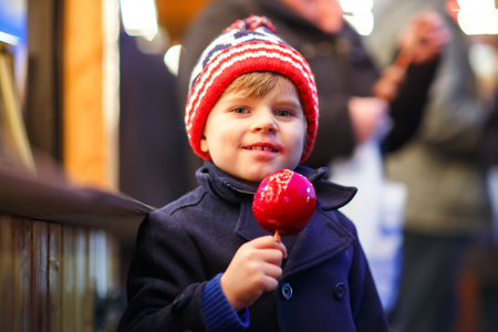 Cute little kid boy eating sweet red apple on German Christmas market. Happy child in winter clothes  with lights on background. Kid looking at the camera. Family, tradition, holiday concept