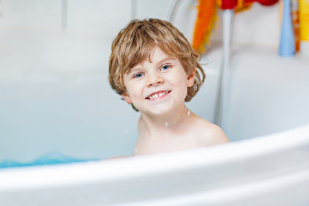 plaything: Cute little child playing with water by taking bath in bathtub at home. Adorable kid boy having fun, washing hair and splashing with soap.