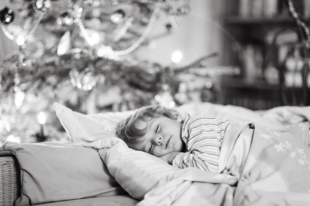 christian festival: Little cute blond boy sleeping under Christmas tree and dreaming of Santa at home, indoors. Traditional Christian festival. Happy kid waiting for gifts.