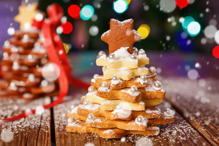 Home made baked Christmas gingerbread tree as a gift for family and friends on wooden background. With colorful lights from Christmas tree on background. With icing sugar gift for xmas. Stock Photo