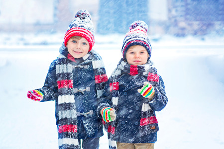 Two little kid boys in colorful clothes playing outdoors during snowfall. Active leisure with children in winter on cold days. Happy siblings and twins having fun with snow Reklamní fotografie