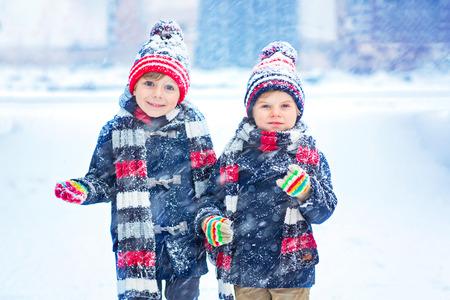 Zwei kleine Kind Jungen in bunten Kleidern spielen im Freien bei Schneefall. Aktive Erholung mit Kindern im Winter an kalten Tagen. Glückliche Geschwister und Zwillinge, die Spaß mit dem Schnee Standard-Bild