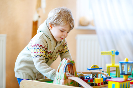 kidsroom: Little toddler boy playing with wooden railway, indoors. Blond funny kid child having fun with toys and learning. Creative leisure. Stock Photo