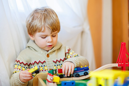 Little toddler boy playing with wooden railway, indoors. Blond funny kid child having fun with toys and learning. Creative leisure. Stock Photo