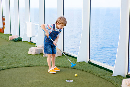 Little kid boy playing mini golf on a cruise liner. Child having fun with active leisure on vacations. 版權商用圖片 - 65993639
