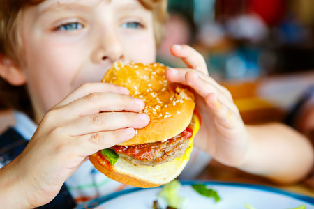 Cute healthy preschool kid boy eats hamburger sitting in cafe outdoors. Happy child eating unhealthy food in restaurant.