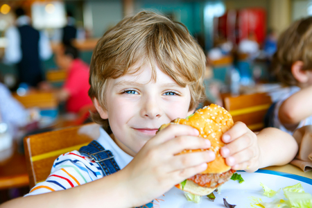 Cute healthy preschool kid boy eats hamburger sitting in cafe outdoors. Happy child eating unhealthy food in restaurant. Imagens - 65993647
