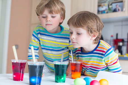 Two funny little friends boys coloring eggs for Easter holiday in domestic kitchen, indoors. Children having fun and celebrating feast. Stock Photo
