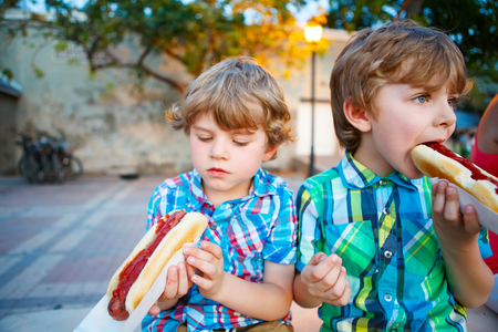 Two little kid boys eating hot dogs outdoors. Siblings enjoying their meal. Hotdog as nhealthy food for children.