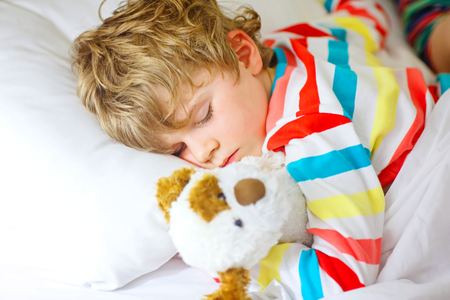 kidsroom: Adorable little blond kid boy in colorful nightwear clothes sleeping and dreaming in his white bed with toy. healthy child with soft toy, peaceful sleep at home.