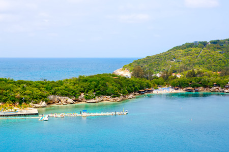 Beach and tropical resort, Labadee island, Haiti. Exotic wild beach with palm and coconut trees against blue sky and azure water
