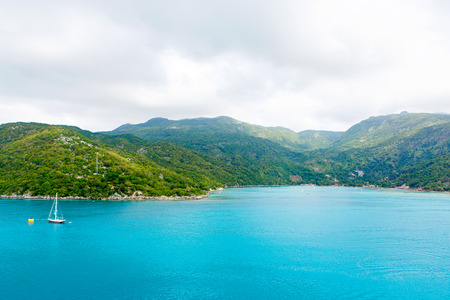 grenada: Beach and tropical resort, Labadee island, Haiti. Exotic wild beach with palm and coconut trees against blue sky and azure water