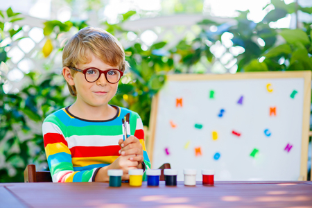 Funny adorable little kid boy with glasses holding wax crayons pens. Happy child and student is back to school. Education, school, learning concept. photo