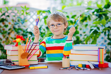 Funny adorable little kid boy with glasses holding wax crayons pens. Happy child and student is back to school. Education, school, learning concept.