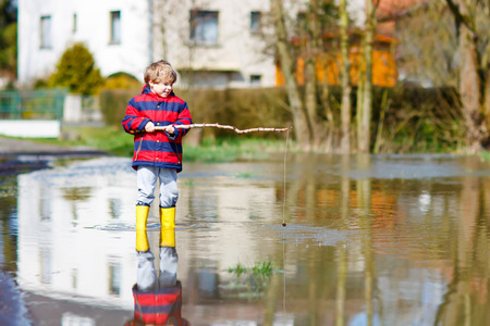 little kid boy in yellow rain boots playing with fishing rod by a puddle on spring or autumn day. Active leisure for children. Child having fun outdoors and wearing colorful clothes.