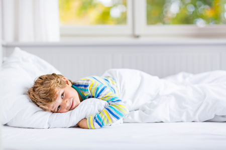 Adorable happy little kid boy after sleeping in his white bed in colorful nightwear near big window with green and yellow autumn foliage. Funny happy child playing and smiling. Family, vacation, childhood concept Stockfoto