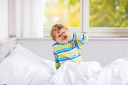 kidsroom: Adorable happy little kid boy after sleeping in his white bed in colorful nightwear near big window with green and yellow autumn foliage. Funny happy child playing and smiling. Family, vacation, childhood concept Stock Photo