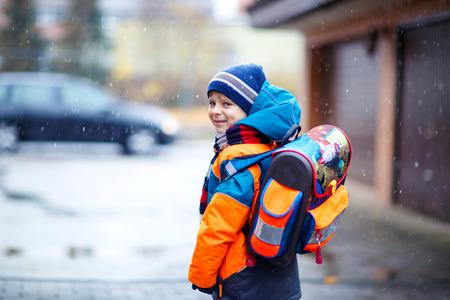 Mały chłopiec dziecko szkoły podstawowej klasy chodzenia do szkoły podczas opadów śniegu. Szczęśliwe dziecko zabawy i zabawy z pierwszym śniegiem. Studentka z plecakiem w kolorowych zimowych ubraniach łapie płatki śniegu.