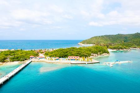 Strand en tropische resort, Labadee eiland, Haïti. Exotisch wild strand met palmbomen en kokospalmen tegen de blauwe hemel en azuurblauwe water Stockfoto
