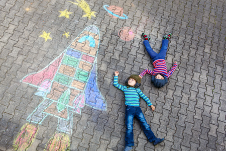 Funny little kid boy flying in universe by a space shuttle picture painting with colorful chalks. Creative leisure for children outdoors in summer. Stock Photo