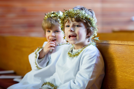 Two beautiful little kids in angel costumes for Christmas story in a church. Happy blond children, boys singing and excited about holiday and Xmas eve. Family celebrating christian and catholic holiday. Stock Photo