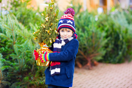 fashion boy: Funny little smiling kid boy holding christmas tree. Happy child in winter fashion clothes choosing and buying xmas tree in outdoor shop. Family, tradition, celebration
