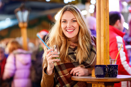 dresden: Beautiful young woman drinking hot punch, mulled wine on German Christmas market. Happy girl in winter clothes with lights on background. Family, tradition, holiday concept