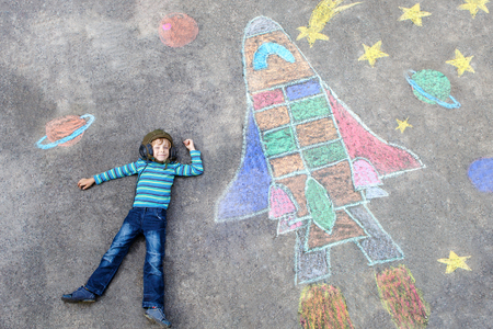 Funny little kid boy flying in universe by a space shuttle picture painting with colorful chalks. Creative leisure for children outdoors in summer. 스톡 콘텐츠