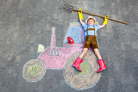 Happy little kid boy in straw hat and rain boots having fun with tractor picture drawing with colorful chalks. Children, lifestyle, fun concept. child dreaming of future and profession. photo