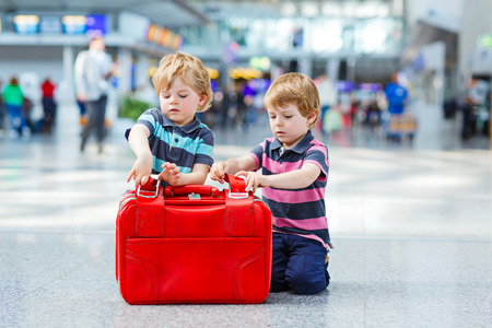 Two little kid boys with suitcases at the airport, indoors and waiting for going on family vacations. Happy children, twins and brothers about exciting air travel trip and flying with airplane. Stock Photo