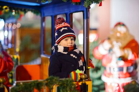 dresden: Funny little kid boy on a carousel at Christmas funfair or market, outdoors. Happy child having fun. Traditional xmas market in Germany, Europe. Holiday, children, lifestyle concept.