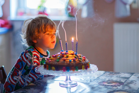 Happy little kid boy celebrating his birthday and blowing candles on homemade baked cake, indoor. Birthday party for children. Carefree childhood, anniversary, happiness. 4 years old Stock Photo