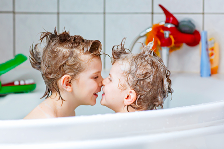 Happy siblings: Two little twins children playing together with water by taking bath in bathtub at home. Kid boys having fun together, helping with hair washing. Stock Photo