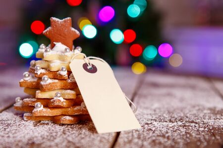 Home made baked Christmas gingerbread tree as a gift for family and friends on wooden background. With colorful lights from Christmas tree on background. With icing sugar als snow. Selfmade gift for xmas. Stock Photo