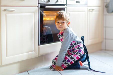 Cute funny blond kid boy baking muffins in domestic kitchen. Child having fun with helping, sitting near ofen and waiting for cupcakes. photo