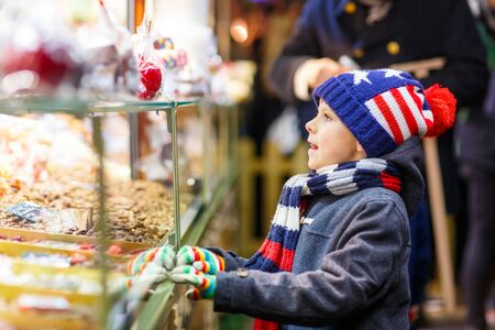 Little cute kid boy near sweet stand with gingerbread and nuts. Happy child on Christmas market in Germany. Traditional leisure for families on xmas. Holiday, celebration, tradition, childhood. Reklamní fotografie