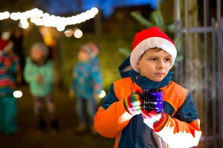 dresden: Little adorable kid boy with cup of steaming hot chocolate or children punch. Happy child on Christmas market in Germany. Traditional leisure for families on xmas. Holiday, celebration, childhood concept. Stock Photo