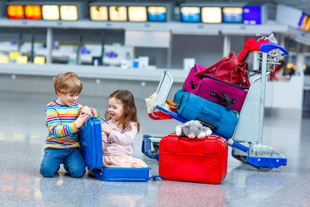 Two little kids, boy and girl with suitcases at the airport, indoors and waiting for going on family vacations. Happy children, twins, brother and sister exciting about air travel trip and flying with airplane.