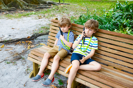 Kids listening to audio guide on excursion. Two little adorable brother boys. photo